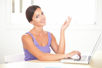 Lovely woman smiling while studying on laptop