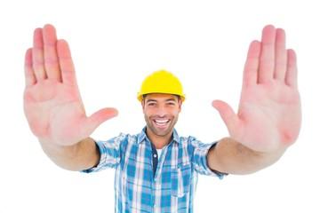 Smiling manual worker gesturing stop sign