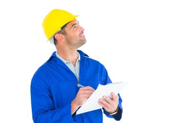 Male supervisor looking up while writing on clipboard