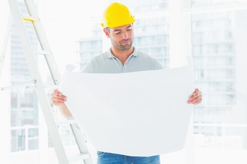 Male architect reading blueprint in office