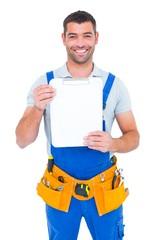 Portrait of happy repairman showing blank clipboard