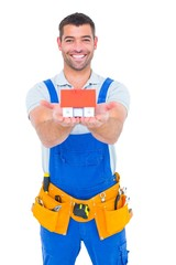 Portrait of happy construction worker holding house model