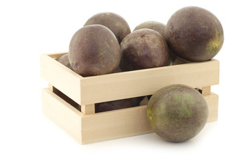 passion fruits and a cut one in a wooden box on a white backgrou