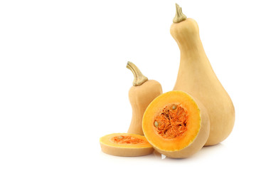 bottle shaped butternut pumpkin and a cut one on a white backgro