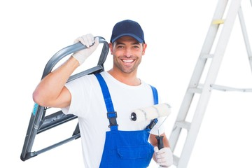 Happy handyman with chair and paint roller on white background