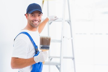 Happy handyman with paintbrush while climbing ladder