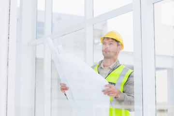 Thoughtful architect holding blueprint in office