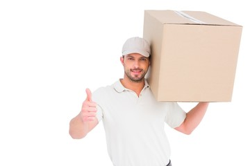 Delivery man with cardboard box gesturing thumbs up