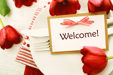 Dinner table setting with Welcome card and red tulips