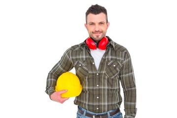 Handyman with earmuffs holding helmet