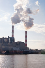 Industrial power plant with two chimneys on the river