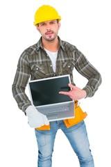 Angry handyman pointing at laptop