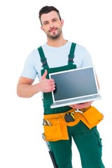 Smiling construction worker holding laptop
