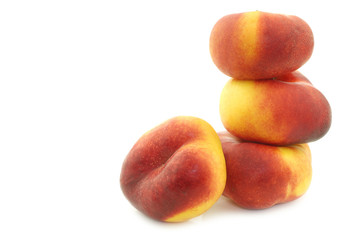 stacked flat nectarines on a white background