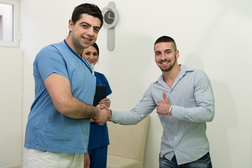 Dentist And Patient Smiling And Hand Shaking