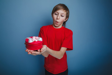 boy teenager European appearance in a red shirt holding a red bo