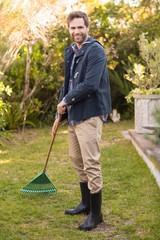 Handsome man raking in his garden
