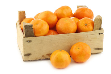 bunch of fresh tangerines in a wooden box on a white background