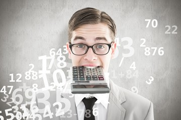 Composite image of geeky smiling businessman biting calculator