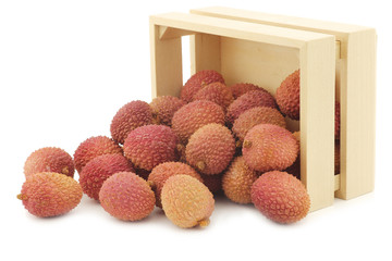 fresh lychees in a wooden box on a white background