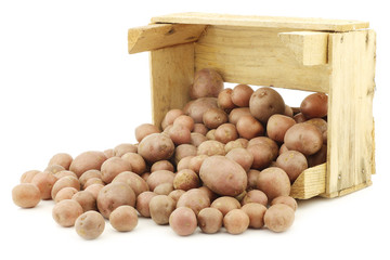 Cherry potatoes (small dutch potatoes) in a wooden crate on a wh