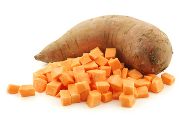 one whole sweet potato and cut blocks on a white background