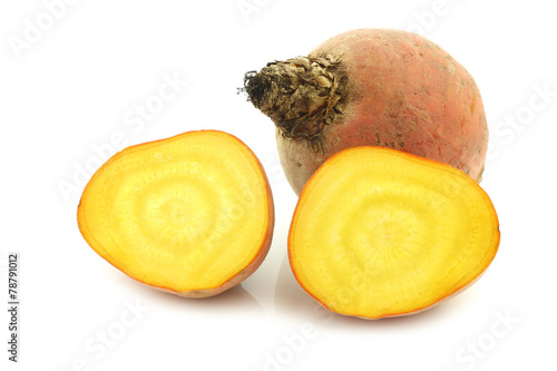 freshly harvested yellow beet and two halves on a white backgrou - 78791012