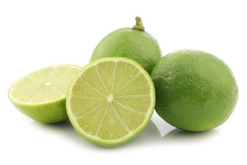 lime fruits and a cut one on a white background