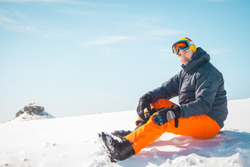 Male skier sitting on snow relaxing