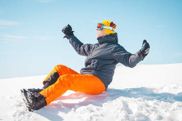 Excited male skier sitting on snow