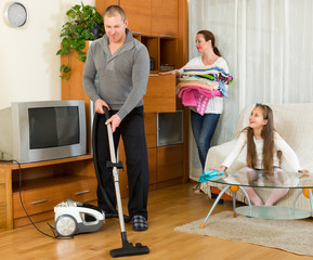 Happy smiling girl helping happy parents to clean at living room