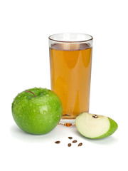 Green apple, glass of juice and three parts of an apple