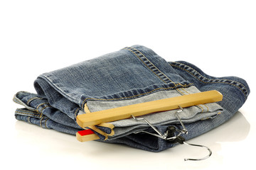 stack of jeans and one with a clothes hanger isolated on a white