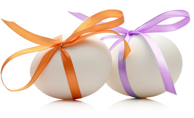 Two Easter eggs with festive orange and purple bow isolated on w