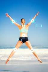 Composite image of fit woman jumping on the beach with arms out