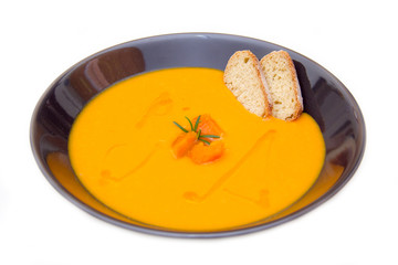 Cream of pumpkin soup with croutons on white background