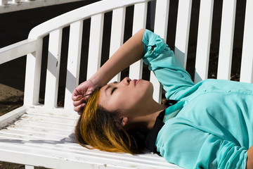 Asian American Woman Reclining Outdoors On Bench