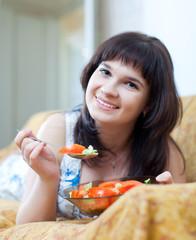 Casual woman eats tomatoes salad