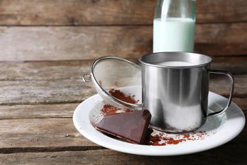 Metal mug and glass bottle of milk with chocolate chunks and