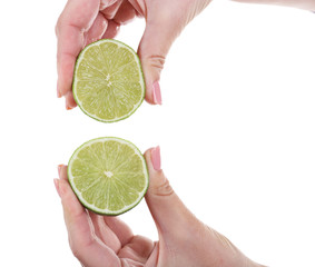 Female hands squeezing lime isolated on white