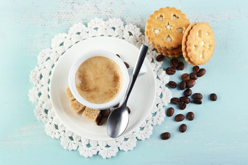Cup of coffee and tasty cookie on color wooden background