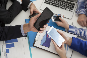Four people are using the smartphone during a meeting