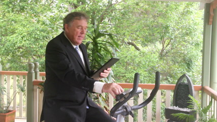 Businessman working out on an exercise bike with his tablet.