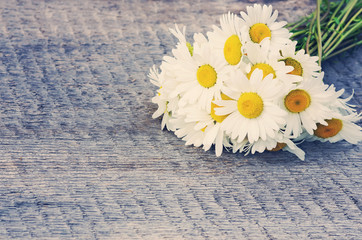 Bouquet of daisies on the board in vintage style