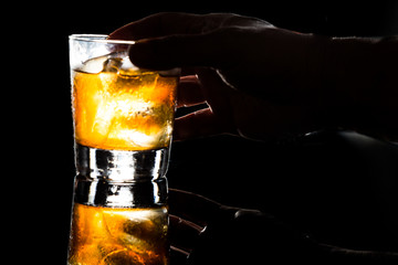 Hand holding a glass of Whiskey on the rocks in dark background