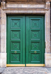 Painted green front door with brass trim in Paris