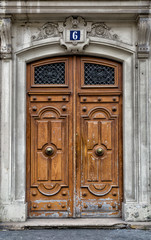 Old wooden front door in Paris. Aged and weathered with great ch