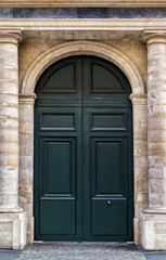 Old wooden front door painted black in Paris