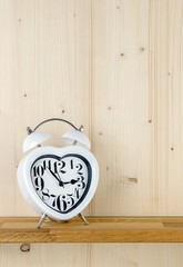 A heart shaped alarm clock on a shelf with copy space background