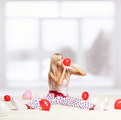 Blonde woman inflating balloons